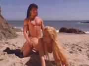 Duży długowłosy facet zapina picz na plaży